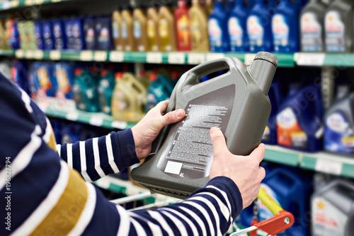 Fototapeta Man buyer chooses oil for car engine in shop obraz