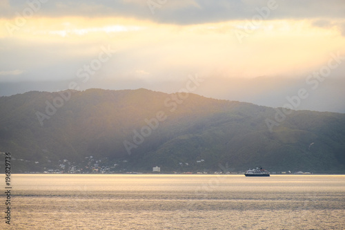 Stunning landscape sunrise in the morning. Ferry on the sea. Golden light go through the cloud to the mountain and sea.