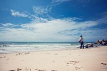 Fisherman Fishing In The Beach Sunny Day