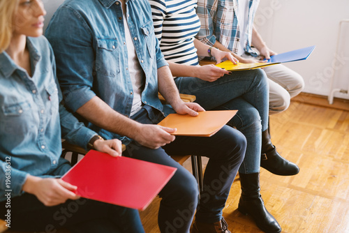 Fotografia  Close up view of young people sitting in chairs with folders before the job interview in the waiting room