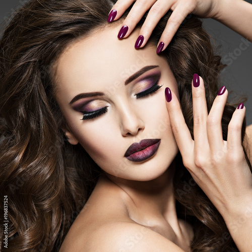 Beautiful face of woman with maroon makeup.