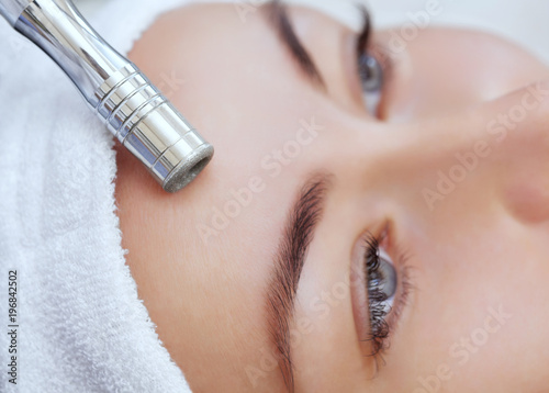 Fotografía  The cosmetologist makes the procedure Microdermabrasion of the facial skin of a beautiful, young woman in a beauty salon