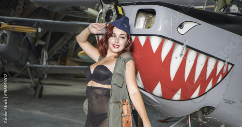Fotografie, Obraz Vintage, redhead woman dressed as a soldier next to a plane of the second world war, American pinup in the style of the 40s