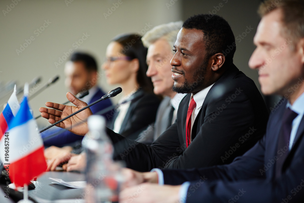Fototapety, obrazy: Young African-american politician explaining his opinion to audience during conference