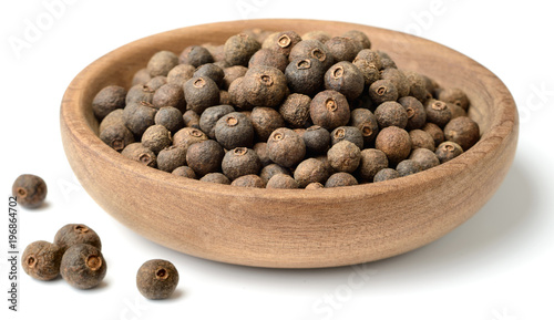 Fototapeta dried herb, allspice in the wooden plate. isolated on white obraz