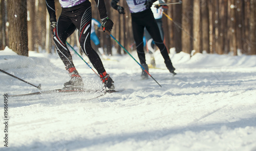 Photo Ski competition - legs of sportsmen running on snowy sunny forest