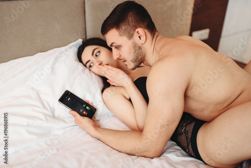 Photo Lovers on big white bed, adultery concept