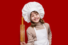 Portrait Of Happy Little Girl In Chef Uniform Holds A Rolling Pin Isolated On Red. Kid Chef. Cooking Process Concept