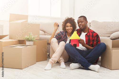 Fényképezés  Black couple sitting on floor at new apartment