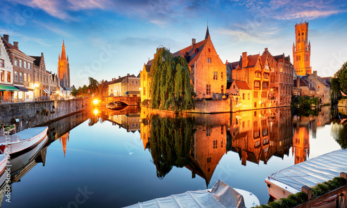 Canal in Bruges and famous Belfry tower on the background at sunset, night, Belgium