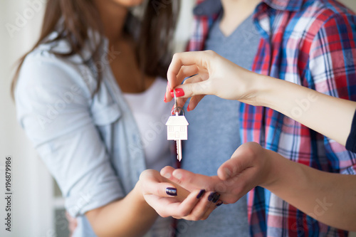 Young Adult Couple Inside Room with Boxes Holding New House Keys Banner Fototapet