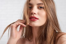 Beautiful Caucasian Model Wearing Eye Make Up And Red Lipstick Playfully Looking To Camera With Half-closed Eyes During Photosession In White Photo Studio. Horizontal Shot, Blurred Background.