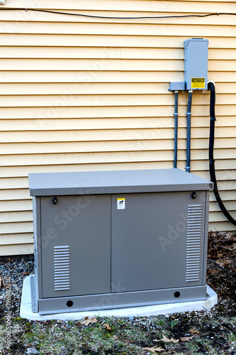 Fotografiet Residential generator on concrete pad, next to a house wall
