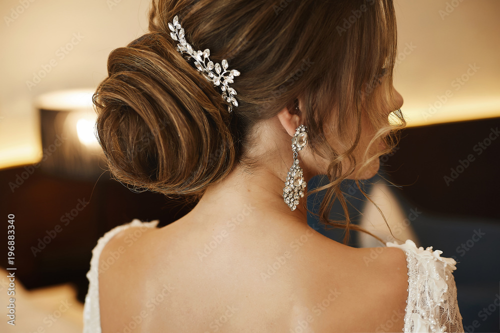 Fototapeta Wedding hairstyle - fashionable brown-haired young woman, in a lace dress and with earrings