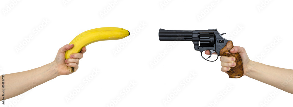 Fototapeta hand with a banana and a hand with gun isolated on white