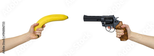 hand with a banana and a hand with gun isolated on white Fototapeta