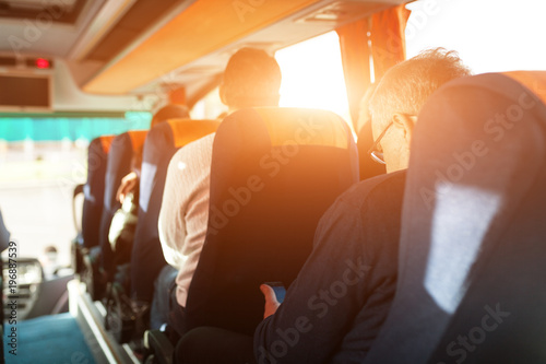 Photo interior of bus with passengers rear view