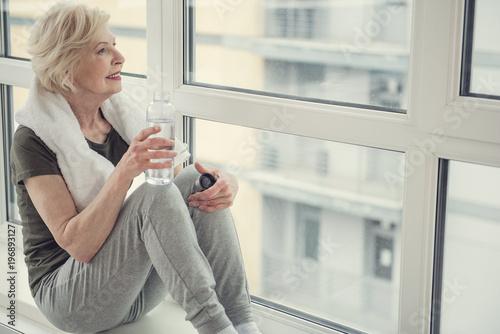Fotografía  Good looking old woman sitting on windowsill with bottle in hand, she is looking out the window with smile