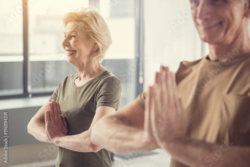 Delighted senior woman standing with hands clasped at her chest and smiling. Old man in same posture standing beside her. Focus on female