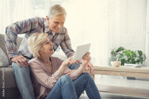 Obraz Happy old woman sitting on the floor and pointing at tablet to her husband. Glad man is resting on couch. Copy space in right side - fototapety do salonu