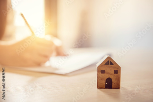 Fototapeta Close up wooden toy house with Woman signs a purchase contract or mortgage for a home, Real estate concept. obraz
