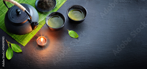 Green Tea In Iron Asian Teapot With Leaves And Bamboo Mat On Black Stone