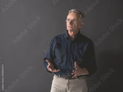 Fotografia Portrait of senior male expressing thoughtfulness while flourishing arms