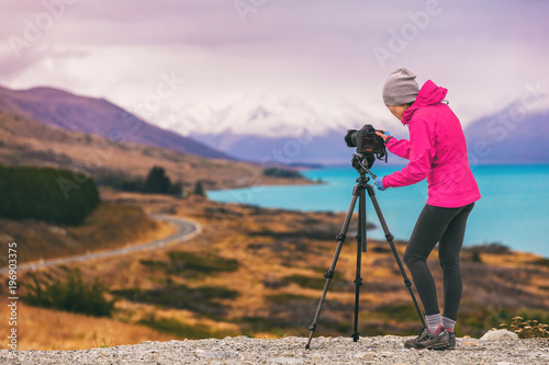Tuinposter Purper Travel photographer woman shooting nature photography mountain landscape at Peter's lookout, New Zealand. Girl tourist on adventure holiday with photo equipment, slr camera on tripod at dusk.