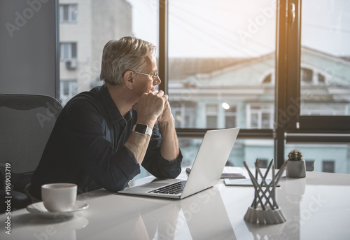 Pensive mature businessman having job with laptop while looking at window Canvas Print