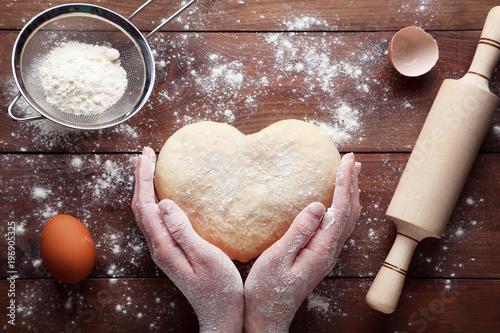 Female hands holding raw dough in heart shape on wooden table Slika na platnu