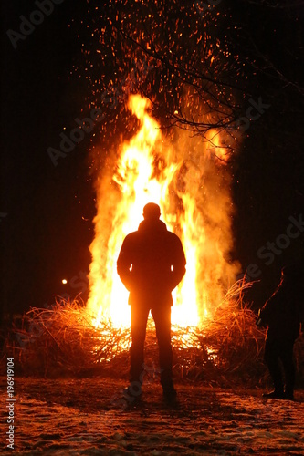 Staande foto Vuur / Vlam Silhouette of man by the fire at night. Man standing in front of bonfire. Flame on the ground.