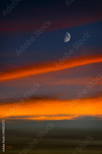 Luna en cuarto menguante se destaca sobre el cielo al atardecer ...