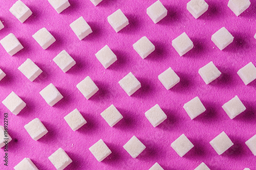 Food background with sugar on purple color paper.
