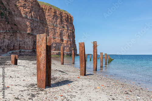 Poster Algérie Beach Helgoland island with red cliffs and rusty iron pillars of old putrefied jetty