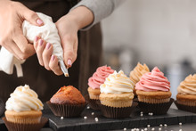 Woman Decorating Tasty Cupcakes With Cream At Table