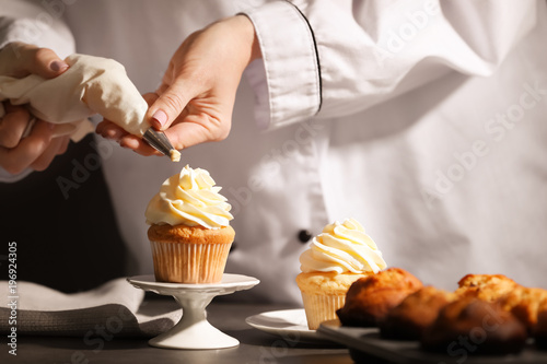 Photo  Chef decorating tasty cupcake with cream at table