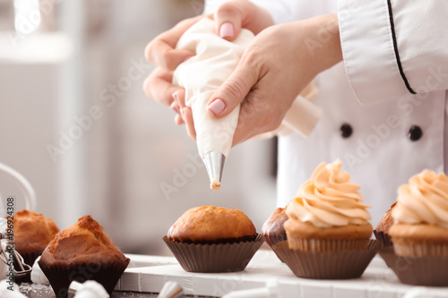 Chef decorating tasty cupcakes with cream at table Canvas Print