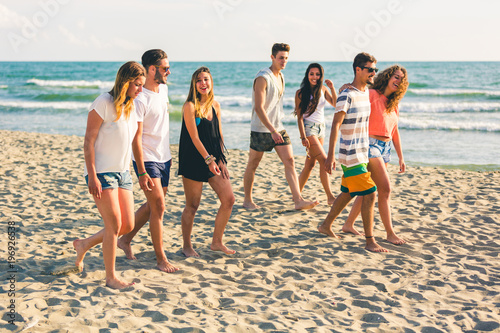 Foto  Multiracial group of friends walking on the beach
