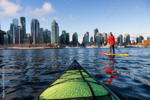 Kayaking and Paddle Boarding in Coal Harbour during a vibrant sunny morning. Taken in Downtown Vancouver, British Columbia, Canada.