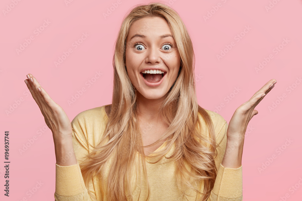 Fototapeta Emotional overjoyed female stares at camera, throws hands up, can`t believe in unexpected success, keeps mouth opened, isolated over pink background. Joy, happiness, excitement, positiveness