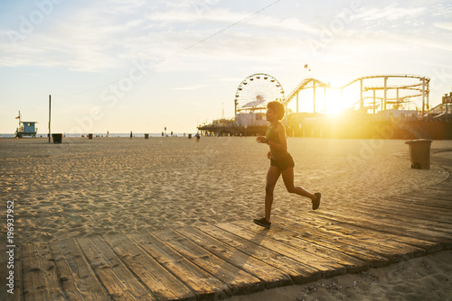 Fotografía athletic african american woman jogging on boardwalk at sunset
