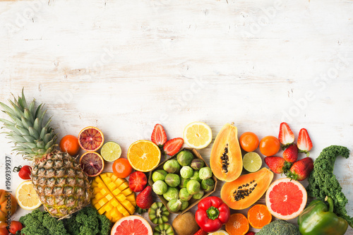 Fototapeta Fruits and vegetables rich in vitamin C, oranges mango grapefruit kiwi kale pepper pineapple lemon sprouts papaya broccoli, on wooden white table, top view, copy space, selective focus obraz