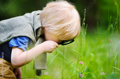 Fotografía  Charming kid exploring nature with magnifying glass