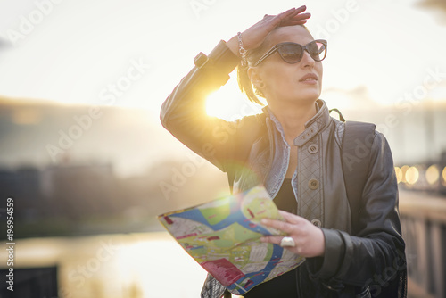 Plakat Confused female tourist in a foreign city using a map, trying to navigate hersel