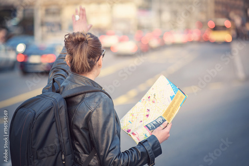Foto  Woman tourist in a foreign city trying to hail a cab, holding a map to navigate