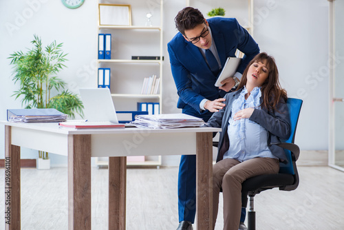 Fototapety, obrazy: Pregnant woman struggling in the office and getting colleague he
