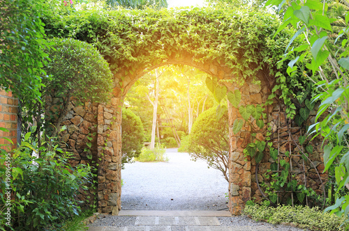 Photo Stone arch entrance gate covered with ivy