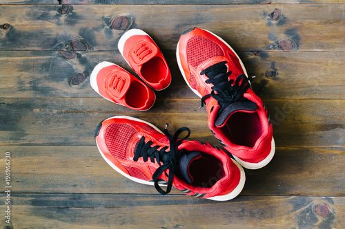 Two red sport running shoes or sneakers of mother or father and child on wooden background,use for father's day or mother's day or family's day with sport concept