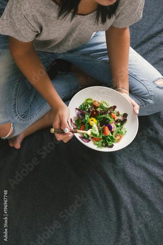 Foto op Canvas Kruidenierswinkel Top view woman eating salad top view Healthy food