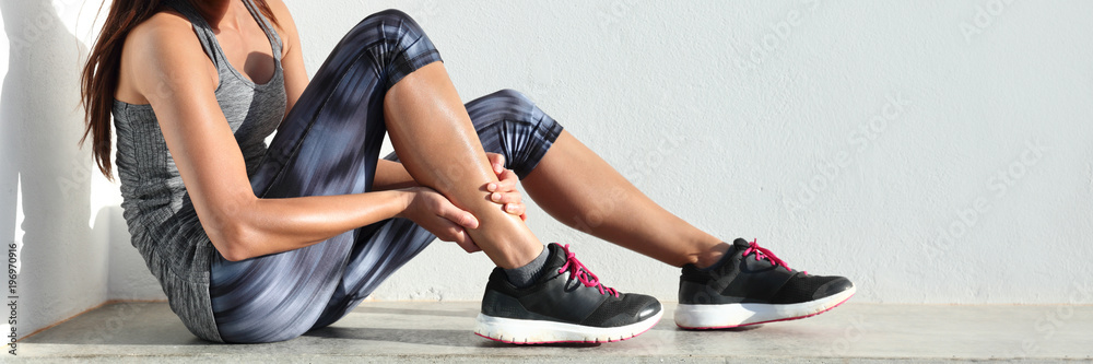 Fototapety, obrazy: Running sport injury leg pain - runner woman runner hurting holding painful sprained ankle muscle. Female athlete with joint or muscle soreness and problem feeling ache banner panorama.